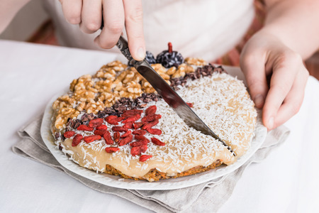 Womans hands cutting raw vegan sweet carrot cake with cream topped with walnuts, goji berries, chocolate truffles, coconut flakes and cocoa crochet Stock Photo