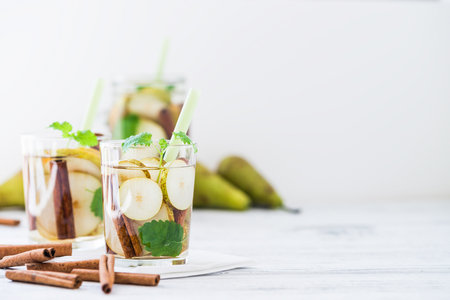 lemon balm: Refreshing drink with pear, cinnamon sticks on white rustic table. Easy to do and tasty summer drink concept. Copy space