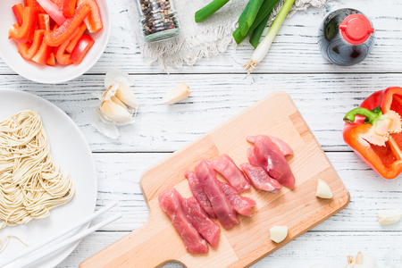 cutting: Fresh raw ingredients for cooking Asian spicy pork on white wooden table, top view
