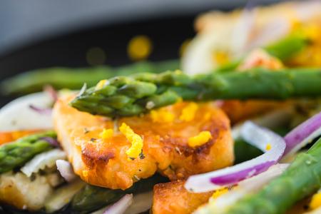 Salad with fried halloumi, asparagus and orange zest. Close up. Dark concrete background