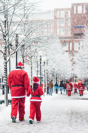 STOCKHOLM, SWEDEN – DECEMBER 11, 2016: Father and daughter dressed up as santas participate in charity event Stockholm Santa Run in Sweden