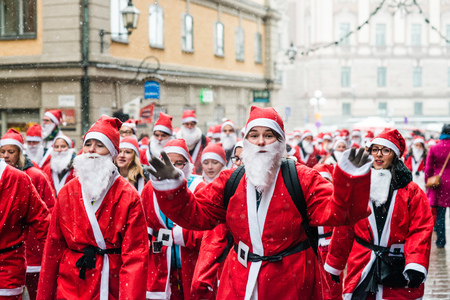 STOCKHOLM, SWEDEN – DECEMBER 11, 2016: Hapy people dressed up as santas run through the Old Town of Stockholm, participating in charity event Stockholm Santa Run in Sweden Editorial