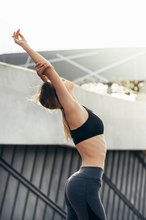 Close up of a fitness woman doing warm up exercises.