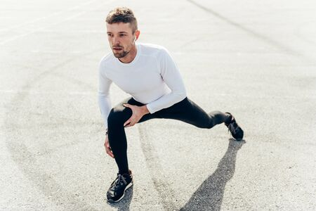 Athlete doing stretching exercise on running.