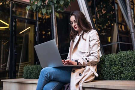 Young attractive businesswoman sitting on the stairs and using modern laptop Foto de archivo