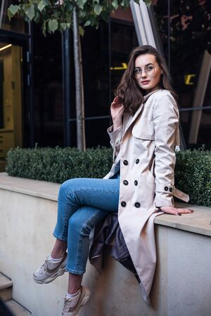 Young attractive woman in trench dreamily looking in camera spending time on cozy city street