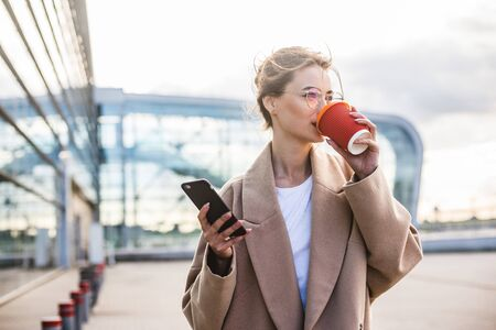 usiness woman using phone near airport entrance,