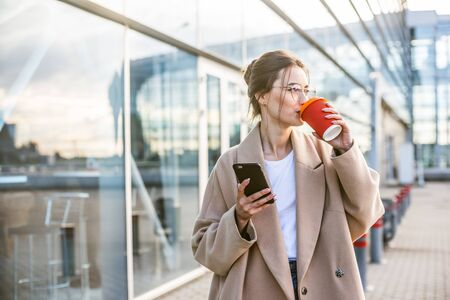 Portrait of young beautiful business woman chatting with smart phone with coffee in her hand near airport building,