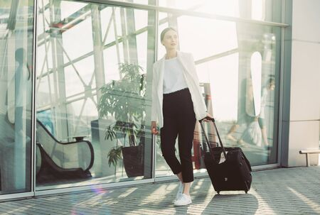 Beautiful mixed race business woman smiling walking in airport lobby looking confident independent female executive enjoying successful corporate career