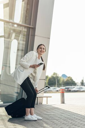Business woman with coffe and talking on the phone near office,