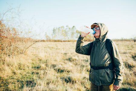 Senior man drinking water in forest.