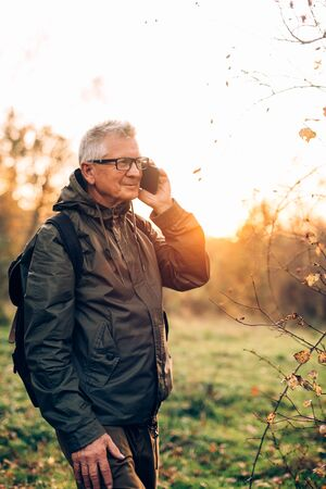 Old man using smartphone in forest.