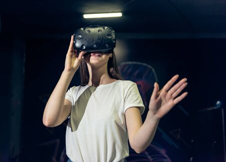 Happy woman on a black background in the studio gets the experience of using VR-glasses virtual reality headset. Stock fotó