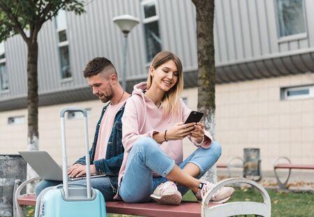 Traveling. Couple using laptop, waiting transport near airport Foto de archivo - 141062785