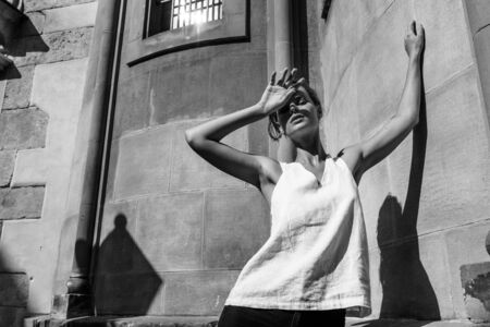 Woman in a white T-shirt standing on the street, shading her face from the sun with shadows