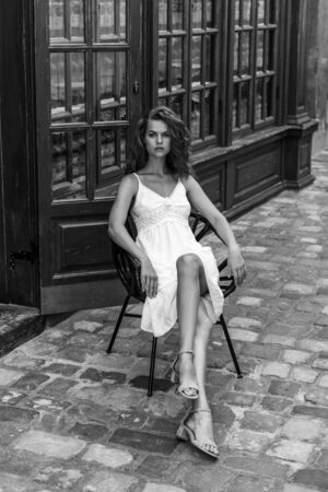 A cute, elegant girl sits on a chair in a street cafe