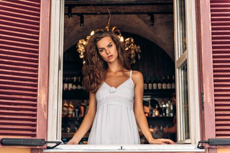 Portrait of laughing young woman looking through window of a cafe Foto de archivo