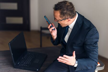 Businessman screaming on mobile phone. Having nervous breakdown at work, screaming in anger, stress management, reaction on failure.
