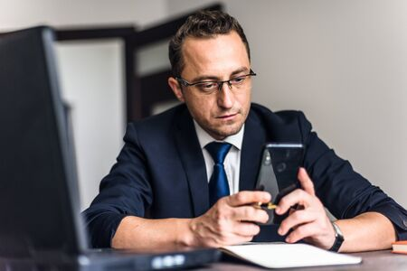 Texting to colleague. Confident young man in smart casual wear holding smart phone and looking at it while sitting at his working place in office.