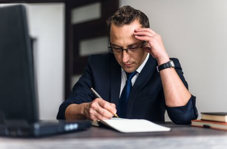 Businessman using mobile laptop computer and taking notes while working at the wooden table office.