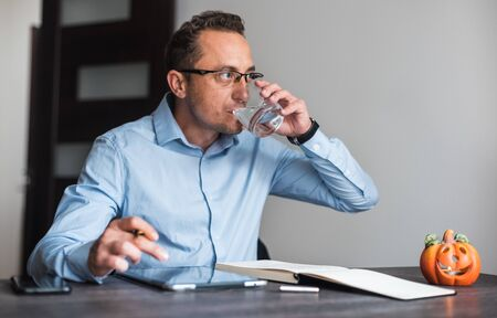Business man at his desk drinking water in office.