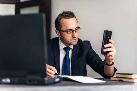 Businessman working in the office. He is using touchpad while reading an e-mail on laptop and taking notes on the paper.