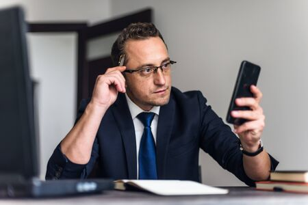 Businessman using phone while working In office. Foto de archivo