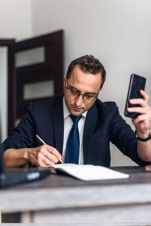Businessman working in the office and use smartphone, documents on his desk.