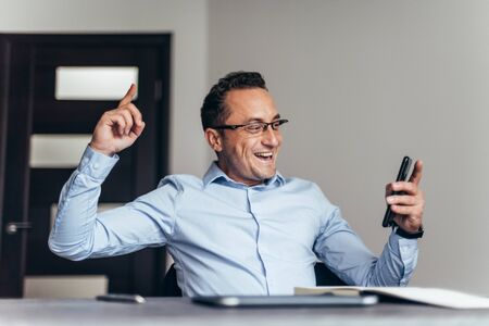 Businessman happy after talking phone about his new career. Foto de archivo