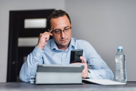 Businessman in formal clothing wearing spectacles using mobile phone
