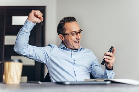 Businessman feeling happy after receiving working e-mail. Feeling happy