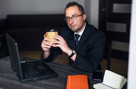 Businessman working at his office via computer, holding coffee.