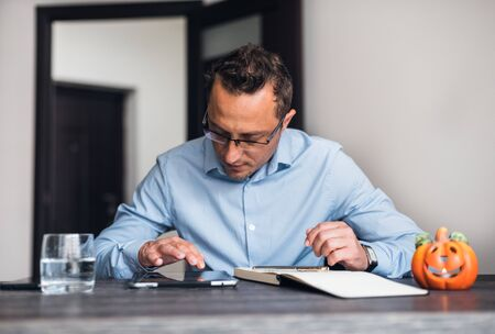 Businessman using a digital tablet at his neat office desk. Foto de archivo