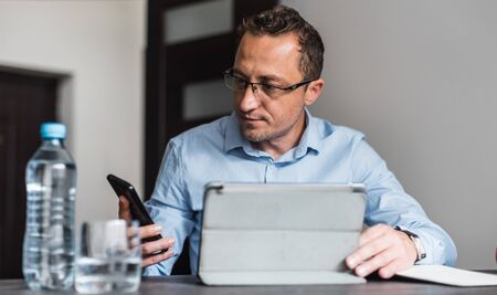 Calm young man in shirt and trousers sitting in the office with a smartphone in his hand and looking at it