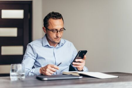 Man working in the office and use smartphone, documents on his desk Foto de archivo