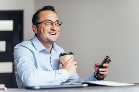 Businessman using phone, holding cup of coffee, sitting at his desk in modern office.
