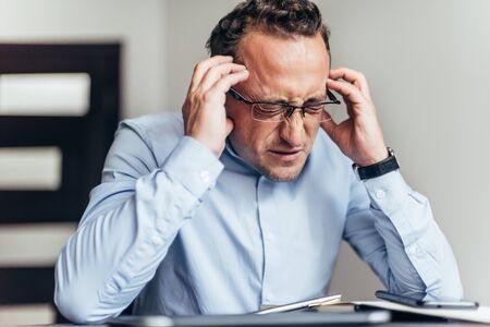Business man suffer headache hold hand head. Businessman feel pain headache stressful day. Stressful business life. Aggression causes headache. Migraine concept.