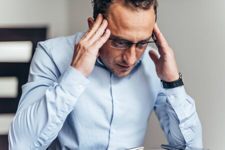 Businessman tired sick stress shocked headache gesture because of bad news on internet, overworked at the office, failure in business concept.