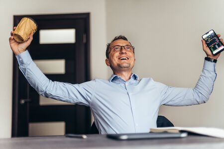 Ecstatic happy executive sales businessman cheering excited in celebration after good news. Foto de archivo