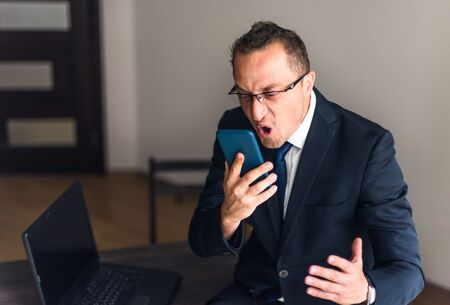 Businessman screaming on mobile phone. Reaction on failure Foto de archivo