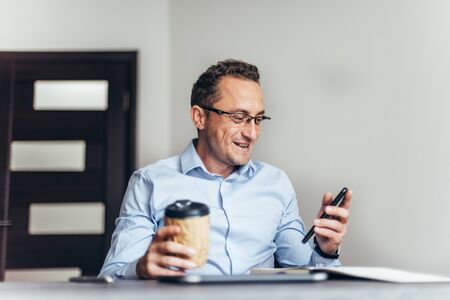 Business is happy after agreed about the successful transaction by phone in office
