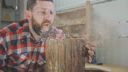 man carpenter in a shirt with a beard blows shavings in the workshop Stock Photo