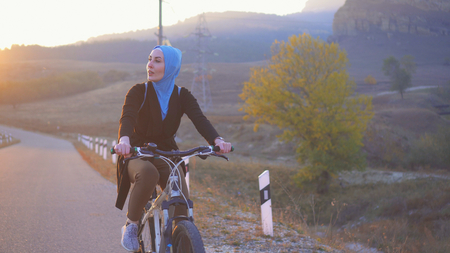 portrait of a muslim woman in hijab riding a bike on the way