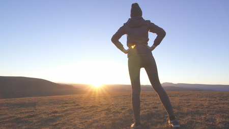 athletic slim woman at a jogging sunrise in the mountains