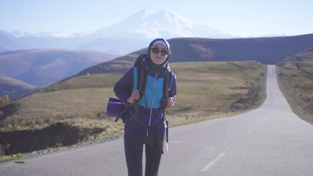 muslim woman tourist with backpack on highway Stockfoto