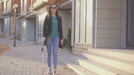 portrait of a blind girl with a cane walking down the street