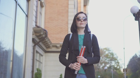 portrait of a blind girl in glasses with a cane on a city street Stockfoto