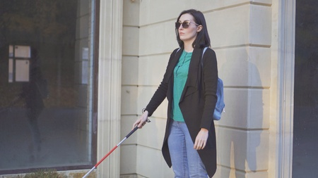 a blind woman wearing glasses with a cane walking in front of shop windows