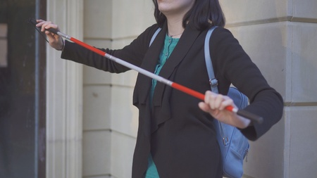 cane for the blind in the hands of a young stylish woman on the street 版權商用圖片