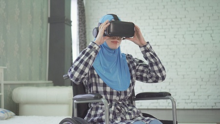 portrait woman in hijab, wheelchair, uses VR glasses, 3D technology